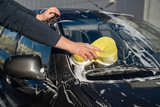 carwash concept. man wash car with soap and yellow sponge