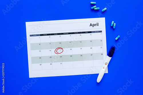 Leinwandbild Motiv Planning pregnancy. Positive pregnancy test near calendar page and pills on dark wooden background top view copy space