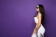 Beautiful and sexy fitness model brunette girl with perfect sporty body in white sportswear with geometric patterns adjusting her stylish sunglasses and pose at violet background