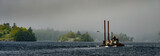 Panorama of Tugboat and barge on a river passing three fog shrouded islands