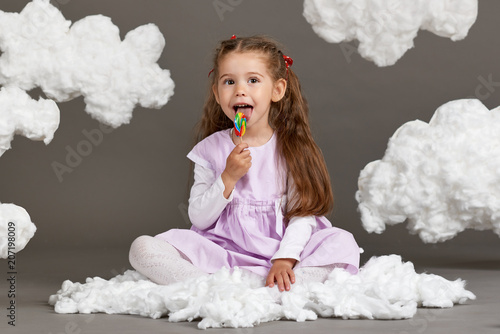 Foto Murales girl girl eating candy and playing with clouds, shooting in the studio on a gray background, happy childhood concept