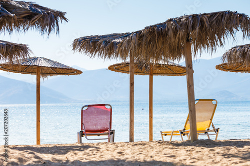 Sun parasols and deck chairs on beach