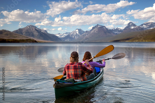 Adventurous traveling couple rowing a boat on a perfect scenic lake in a beautiful national park