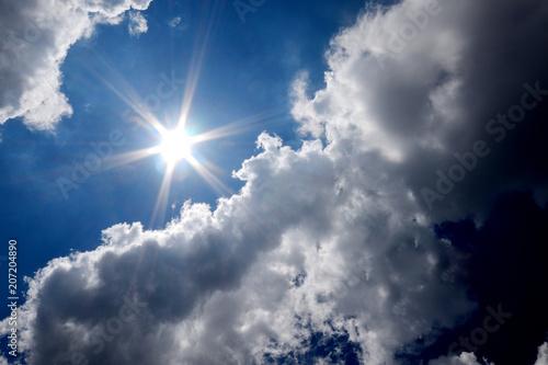 Dark clouds with sun on blue sky.