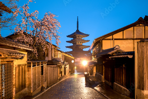 Fotobehang Kyoto Japanese pagoda and old house with cherry blossom in Kyoto at twilight.
