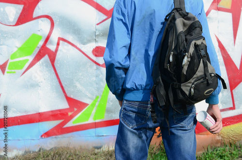 A young graffiti artist with a black bag looks at the wall with his graffiti on a wall. Street art concept