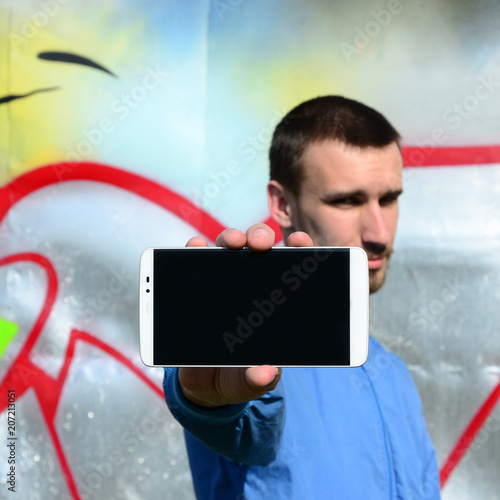 The graffiti artist demonstrates a smartphone with an empty black screen against the background of a colorful painted wall. Street art concept