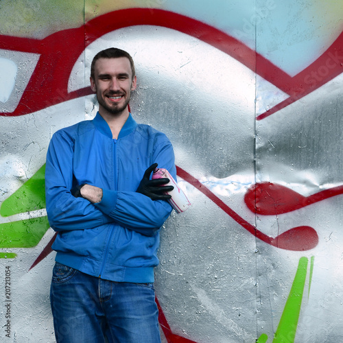 The graffiti artist with spray can poses against the background of a colorful painted wall. Street art concept