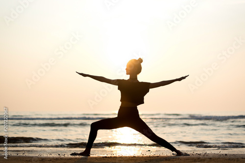 Fototapeta Young healthy woman practicing yoga on the beach at sunset