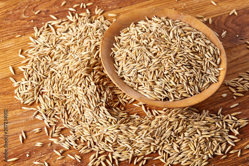 Oat groats or oat spike in wooden plate on old wooden background