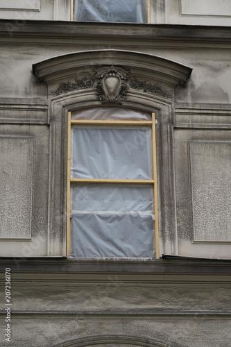 Foto Murales fenêtres avec feuilles plastiques. Façade en rénovation.