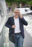 Businessman walking in the street, talking on phone