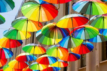 Multicolored, rainbow, umbrellas hung over the street.