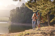 Couple Enjoying Walk By Lake On Family Hiking Adventure - 207257490