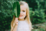 Little girl holding green leaf covering face, closeup - 207261027