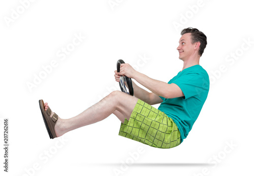 Happy man in shorts and slippers driving a car with steering wheel, isolated on white background