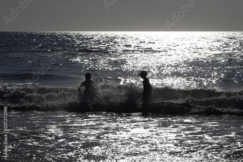 Fotobehang Noordzee Zwei Kinder spielen in den Wellen der Nordsee bei Sonnenuntergang