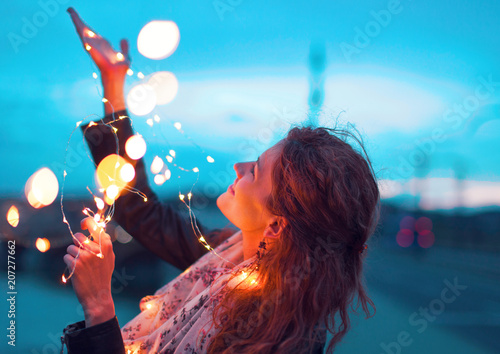 Foto Murales Happy woman playing with fairy light garland at evening