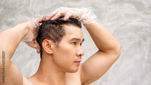 Asian men dye his hair color on a gray background.