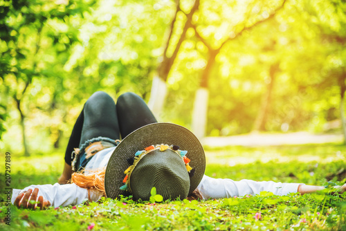 Plexiglas Geel Asian woman travel nature. Travel relax. sleep on the lawn in the park. in summer.
