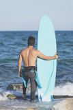 Young attractive surfer holding his surfboard at the beach - 207312055