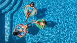 Aerial top view of family in swimming pool from above, happy mother and kids swim on inflatable ring donuts and have fun in water on family vacation, tropical holidays on resort  - 207313852