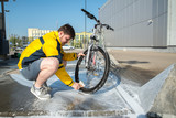 young man clean bicycle with soap and sponge at carwash self-service. lifestyle - 207320020