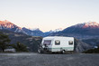 Caravan with a bike parked on a mountaintop with a view on the french Alps near lake Lac de Serre-Poncon