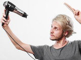 Young man drying hair with hairdryer - 207325848