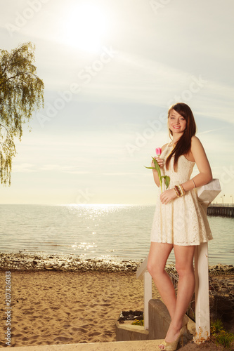 Woman standing on beach holding pink tulip