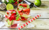 fresh lemonade with strawberries , lime and mint on a wooden background