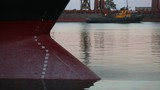 Panorama of submerged into the water freighter bow of ship under the cargo weight. Draft marks on a bulker - waterline numbers on bow and stern of a vessel at seaport in the evening - 207333241