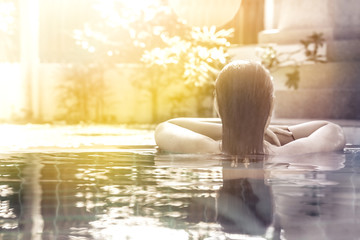 woman relaxing in hotel spa swimming pool looking at view with sunlight and copy space