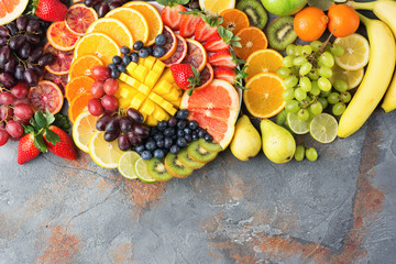 Healthy fruits background in rainbow colours oranges apples grapes pears mango strawberries kiwis on the grey brown concrete table, top view, copy space, selective focus