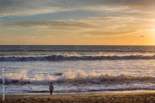 Plexiglas Bali Unidentified woman watching the sunset on Seminyak beach, Bali, Indonesia