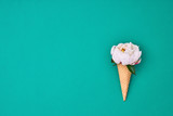Ice cream cone with white peony flowers and leaves on green background. Summer concept. Copy space, top view