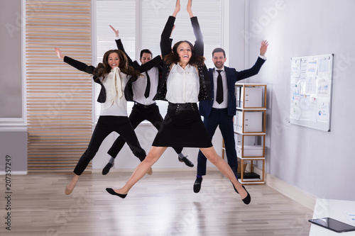 Poster Young Businesspeople Jumping In Office