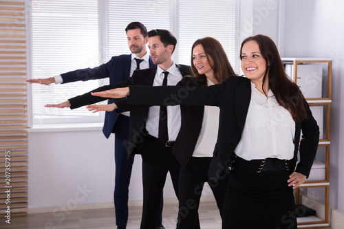 Plakat Businesspeople Doing Exercise With Hands Outstretched