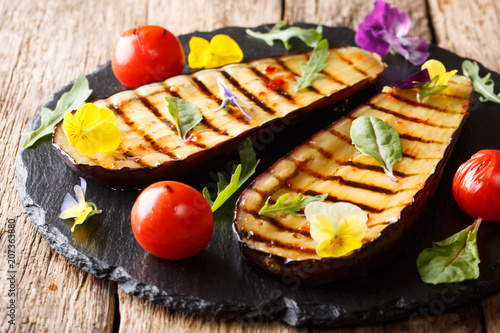 delicious healthy grilled aubergines and tomatoes with herbs and edible flowers close-up. horizontal - 207363880