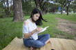 Asian women sit reading at the park.