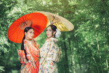 Asian girl wears a kimono and holds a traditional Japanese umbrella. - 207371263