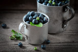 Sweet blueberry in the old metal mug on wooden table - 207374689