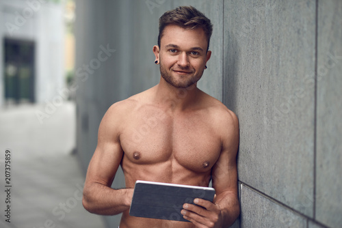Młody mięśniowy mężczyzna czyta na pastylce
