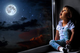 the child looks out the window into the night sky - 207376834