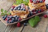 Yummy sweet waffles with raspberries and blueberries on a wooden table .