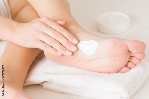 Fotobehang Pedicure Groomed woman's hand applying feet moisturizing cream. Barefoot on the white towel. Cares about clean and soft legs skin. Healthcare concept.