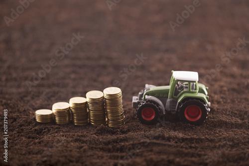 Fotobehang Trekker Tractor miniature with coins on fertile soil land