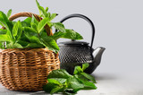 fresh mint in a wicker basket and tea pot, on a graduated background - 207385291
