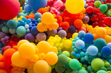 Fototapeta Tęcza - Bright abstract background of jumble of rainbow colored balloons celebrating gay pride © lazyllama