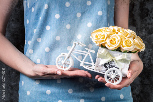 Fotobehang Fiets Wedding handmade decor: The girl holds a small bouquet of roses in her hands in a decorative box in the form of a bicycle. Close-up of hands.